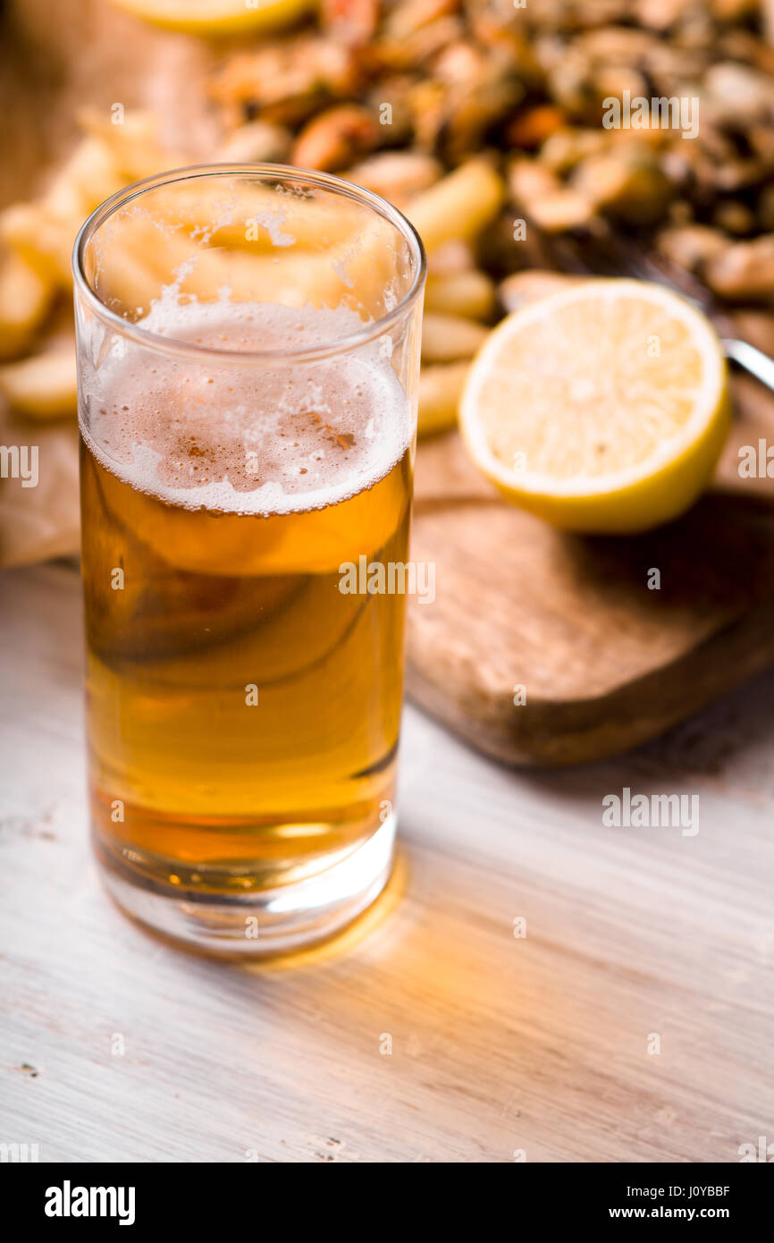 Glass of beer with blurred snack on the white wooden table - Stock Image