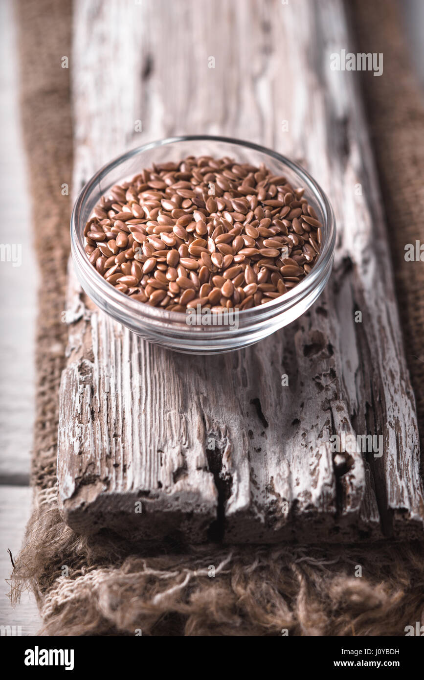Flax seed on the wooden board vertical - Stock Image