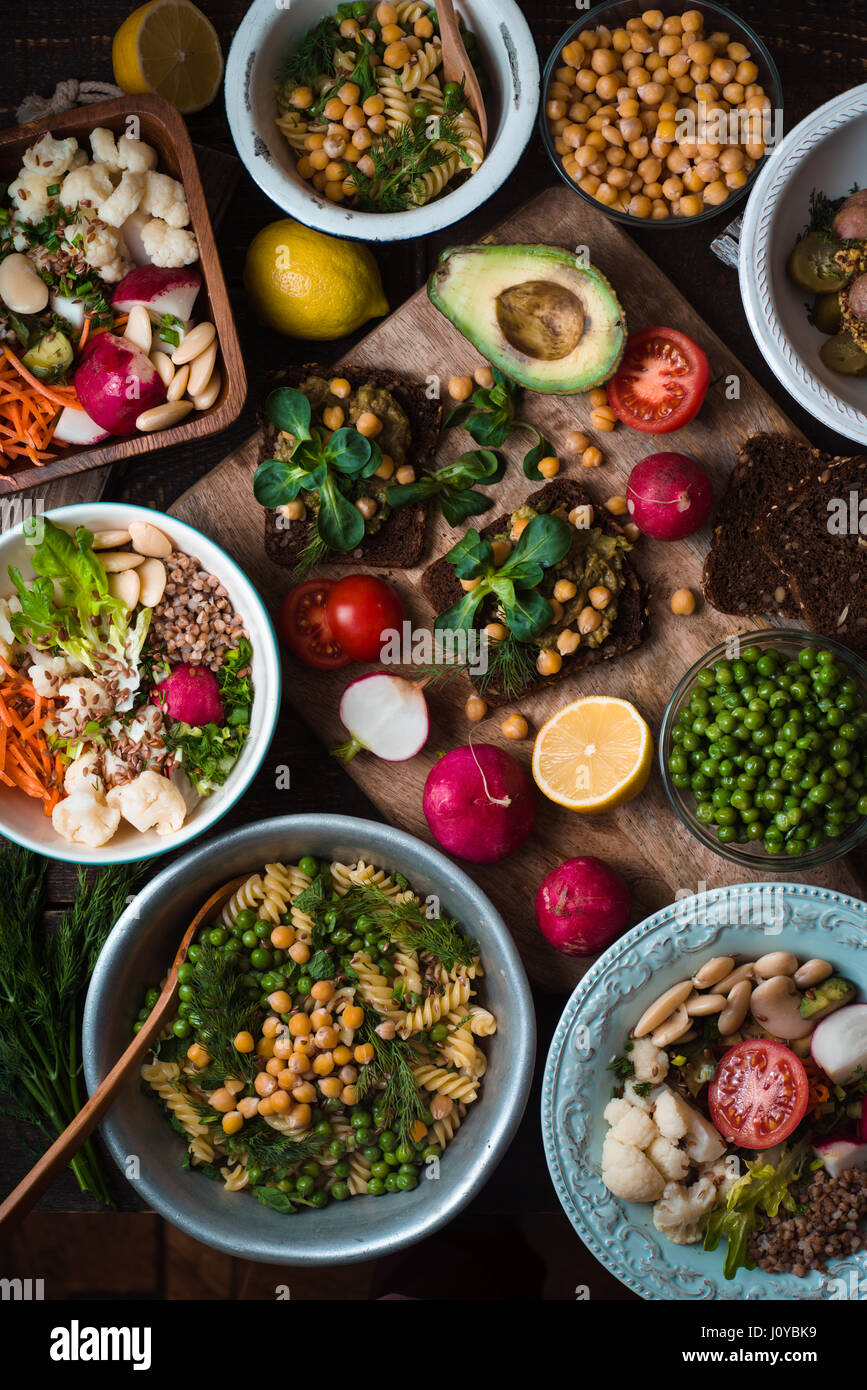 Different salad and appetizer on the wooden table top view - Stock Image