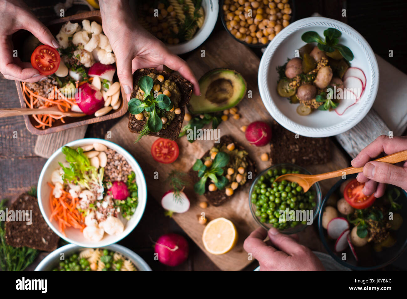 Eating different salad and appetizer on the wooden table top view - Stock Image