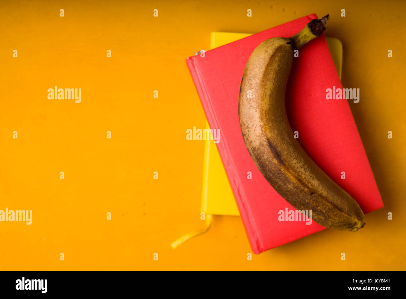 One banana on notepads on a bright background - Stock Image