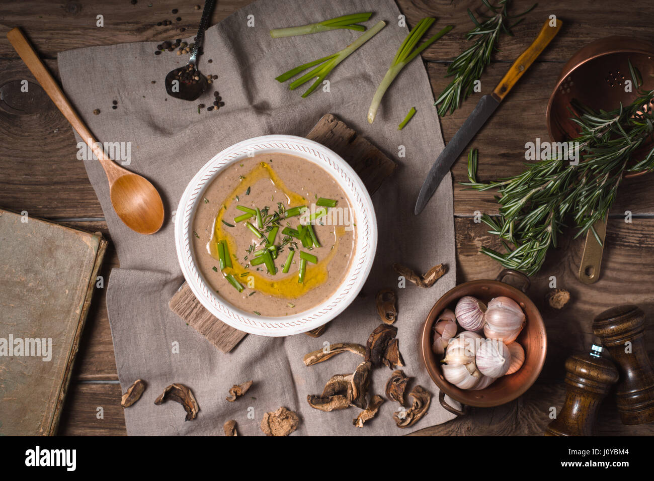 Mushroom cream soup on rustic background, top view - Stock Image