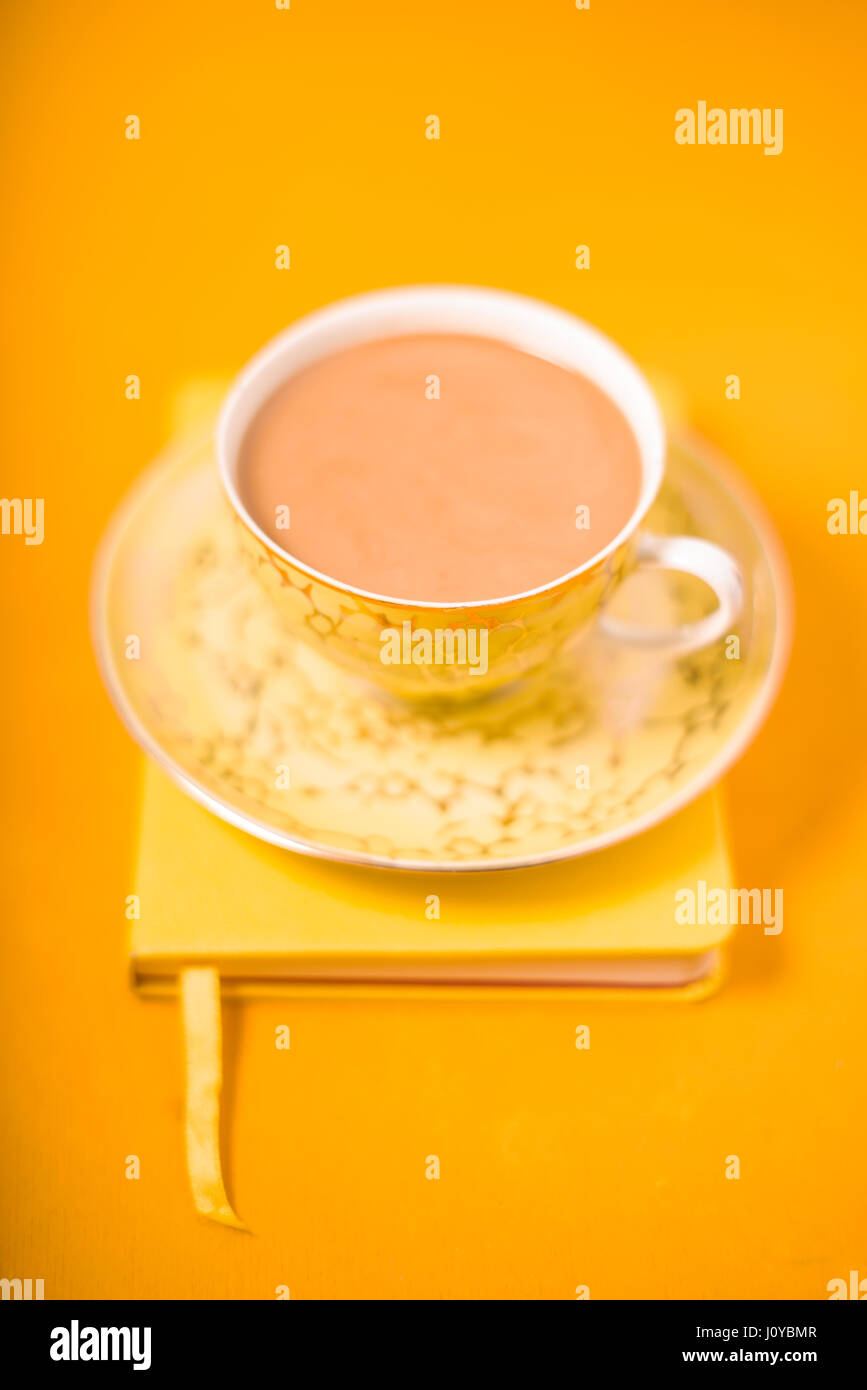 Cup and saucer and coffee with milk on a yellow background - Stock Image