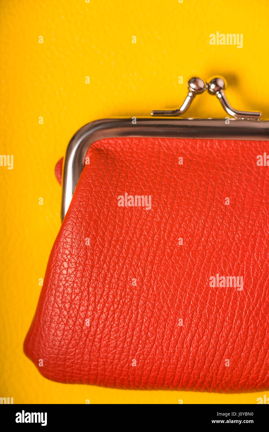 Orange purse on a wooden yellow table - Stock Image