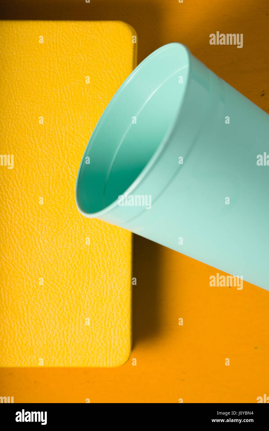 Plastic turquoise glass and notebook on a yellow background - Stock Image