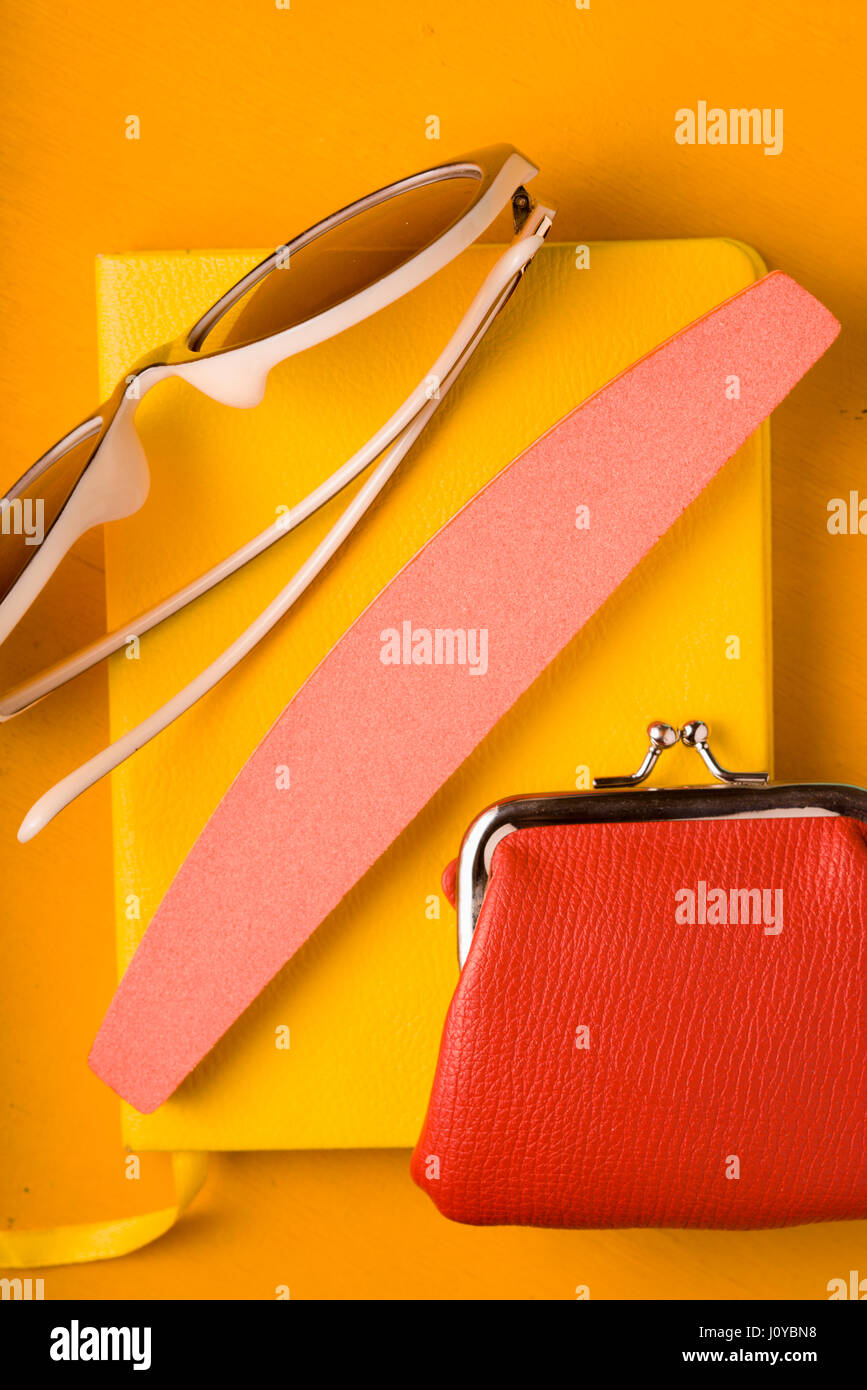 Glasses, purse on a notepad on a yellow pop art background - Stock Image