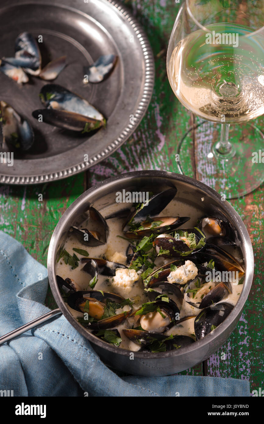Mussels in leaves in sauce on a tin plate and in a saucepan Stock Photo