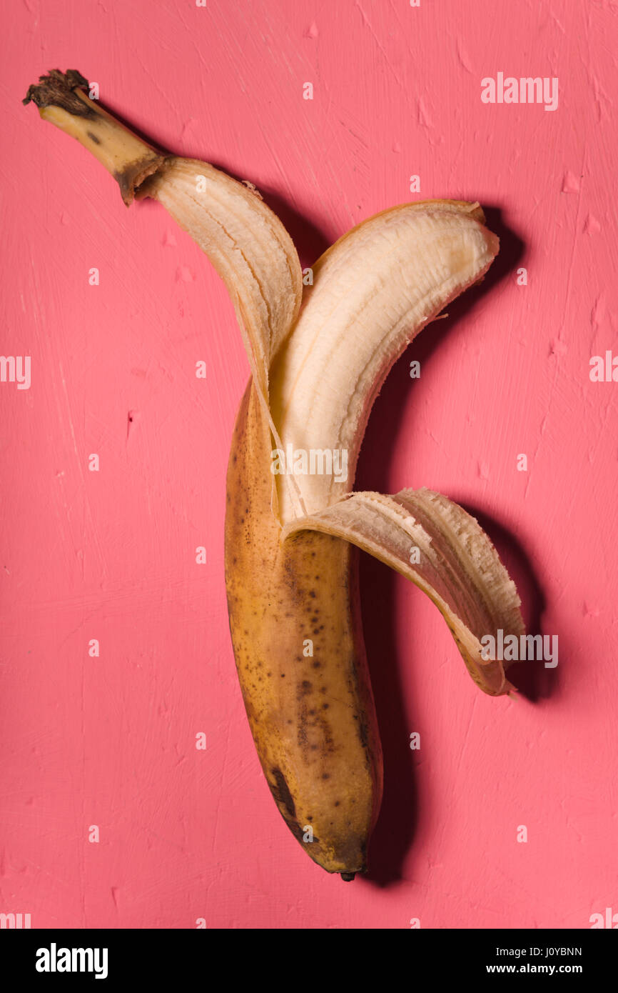 Kitsch styling banana peeled on a pink background - Stock Image