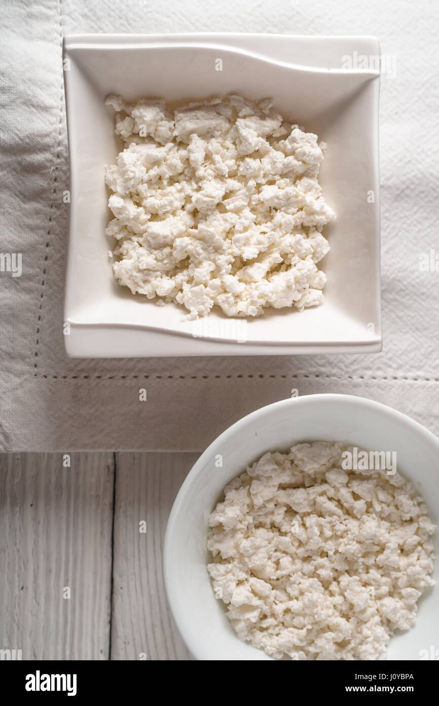 Cottage cheese in ceramic bowls on a linen napkin - Stock Image