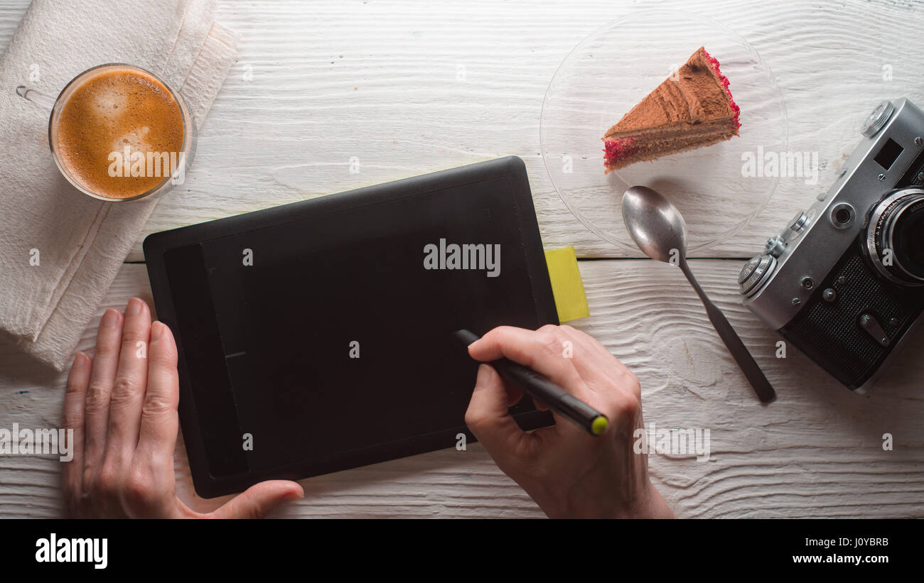 Tablet, camera, coffee cup, cake on white table - Stock Image