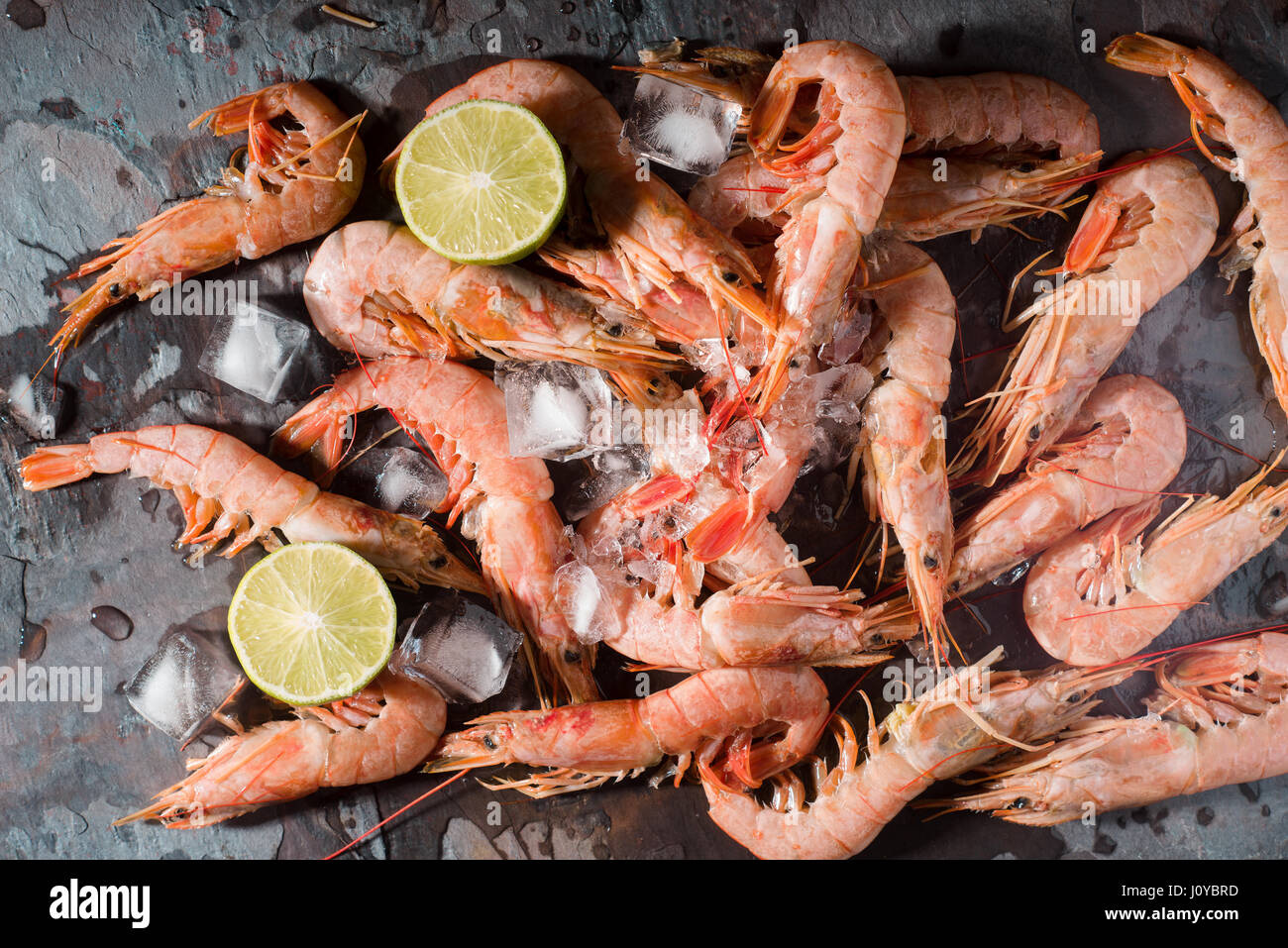 Fresh shrimps served on a gray slate with lime and ice - Stock Image
