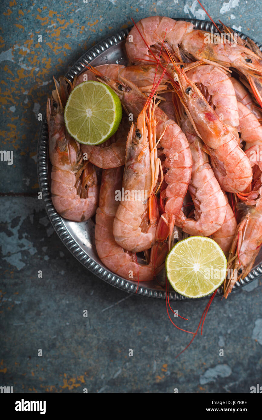 Large shrimps and lime on a tin plate - Stock Image