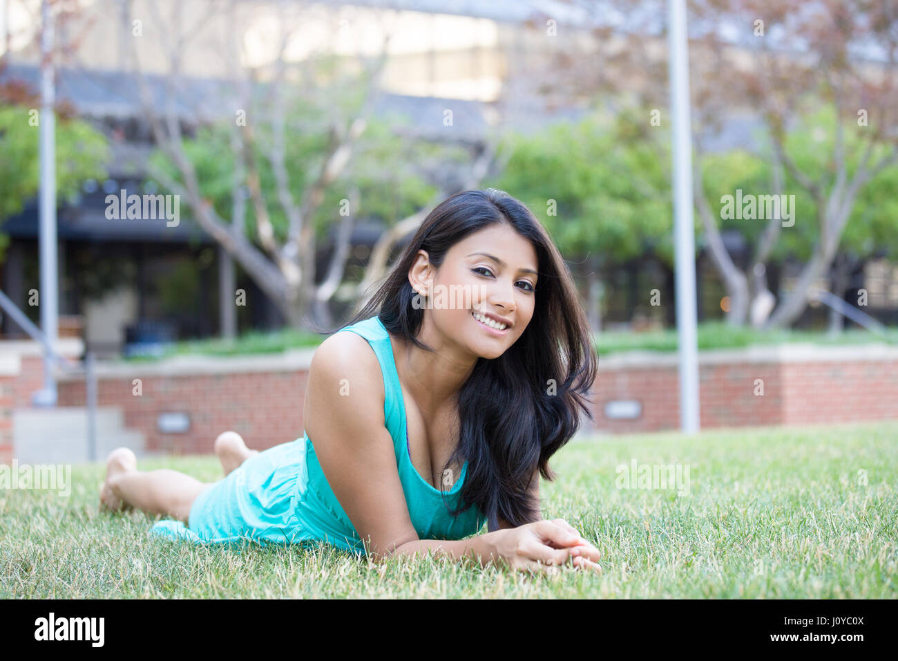 Closeup portrait, beautiful woman in blue green dress lying on stomach on grass, isolated outside outdoors trees - Stock Image
