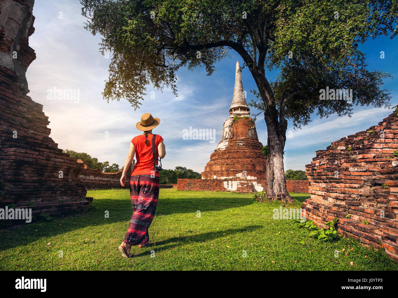Tourist Woman in red costume walking near ancient ruined stupa with photo camera in Ayutthaya Historical Park, Thailand - Stock Image