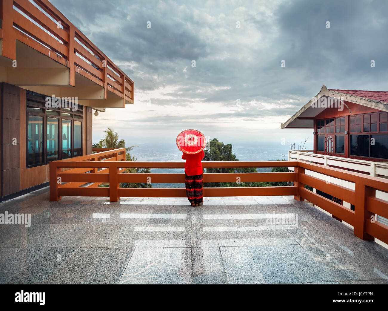 Woman with red Thai umbrella at view point looking at Chiang Mai city panorama at sunset in Thailand - Stock Image