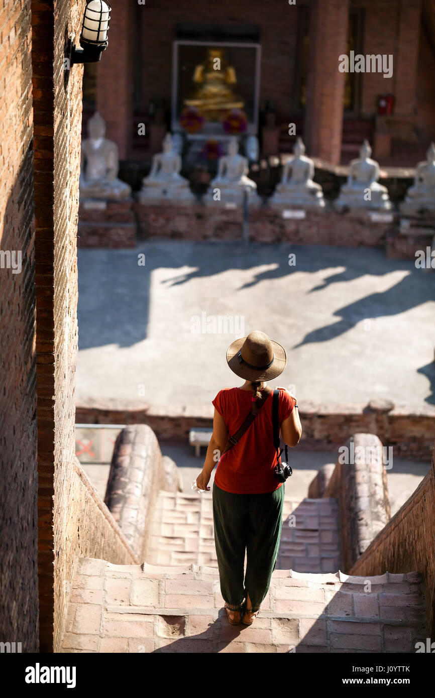 Tourist Woman in hat and photo camera in ancient Buddhist complex in Ayutthaya Historical Park, Thailand - Stock Image