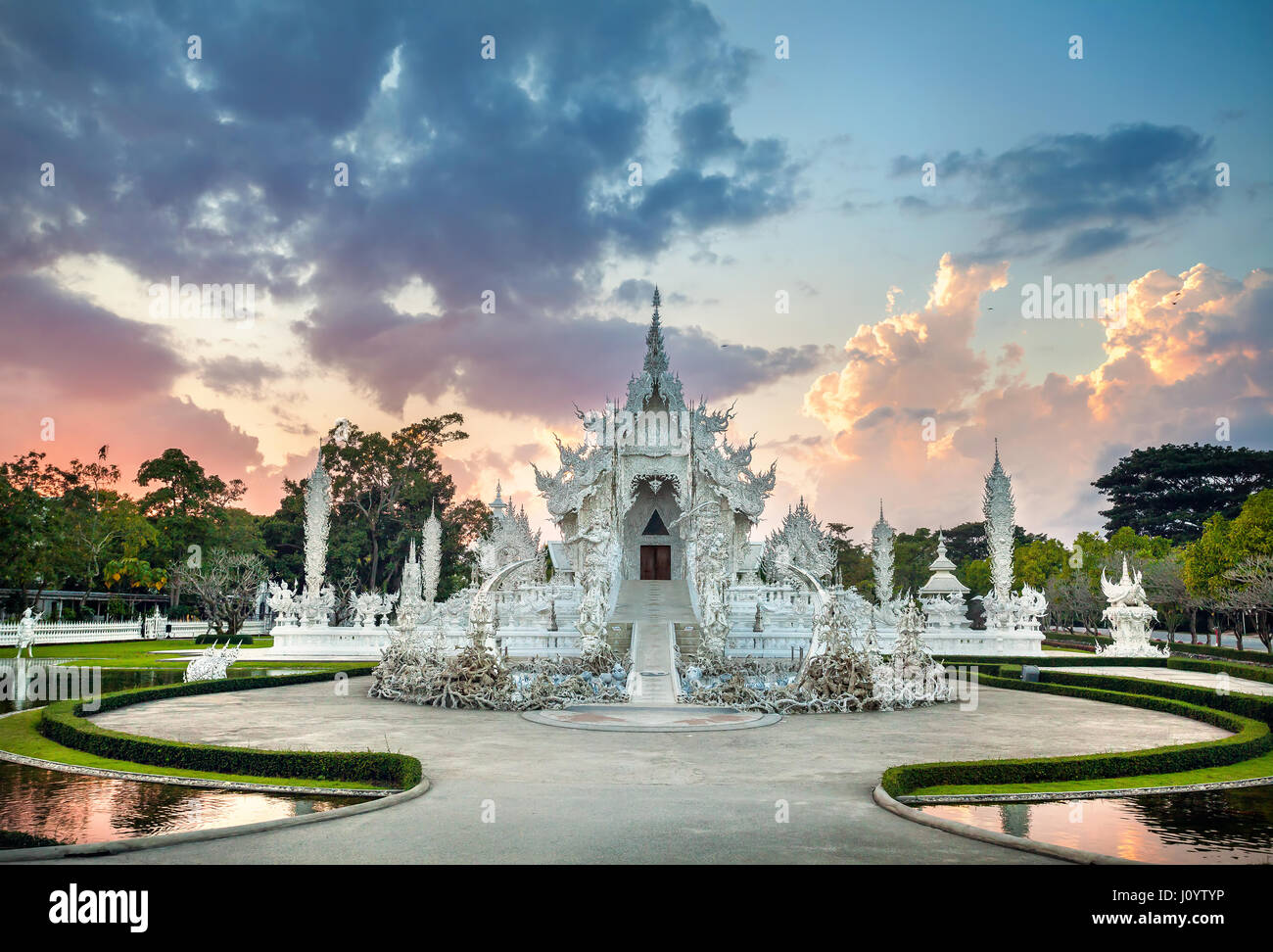 Wat Rong Khun The White Temple and pond at dramatic sunset background in Chiang Rai, Thailand - Stock Image
