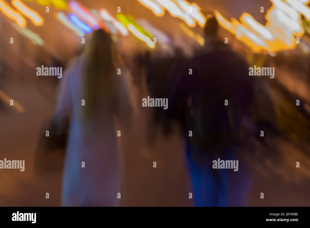 Abstract vintage tone motion. Blurred image of Street, girl and guy walking along the sidewalk city lights. Concept - Stock Image