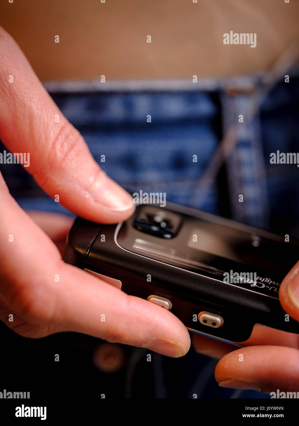 A woman with Type 1 diabetes using an insulin pump and constant  a glucose monitor. - Stock Image
