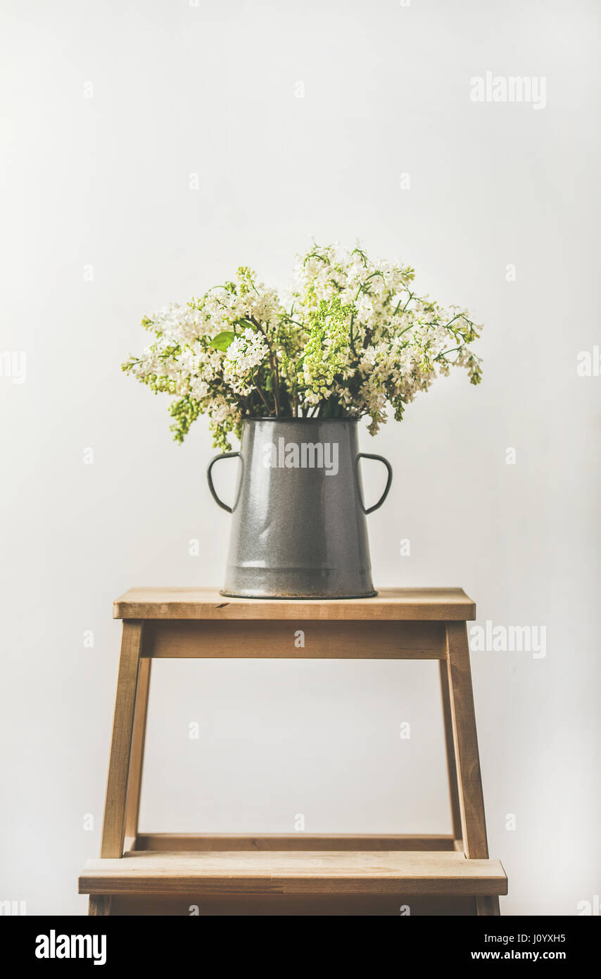 Spring bouquet of white lilacs in vintage gray enamel vase - Stock Image