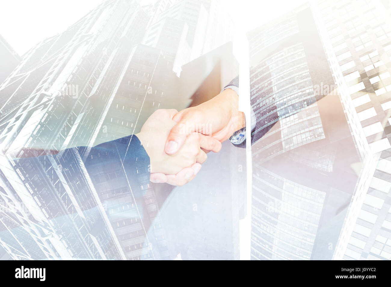 Double exposure of Close up businesswoman and businessman handshake with cityscape building, Business partnership - Stock Image