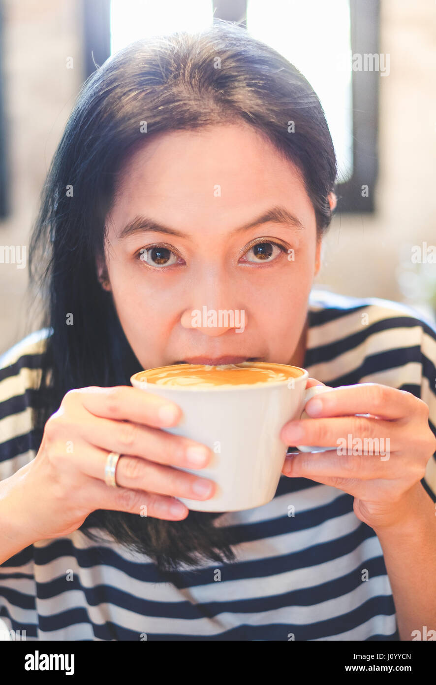 Close up face of asian woman sip hot cappuccino coffee in cafe shop,drinking hot beverage. - Stock Image