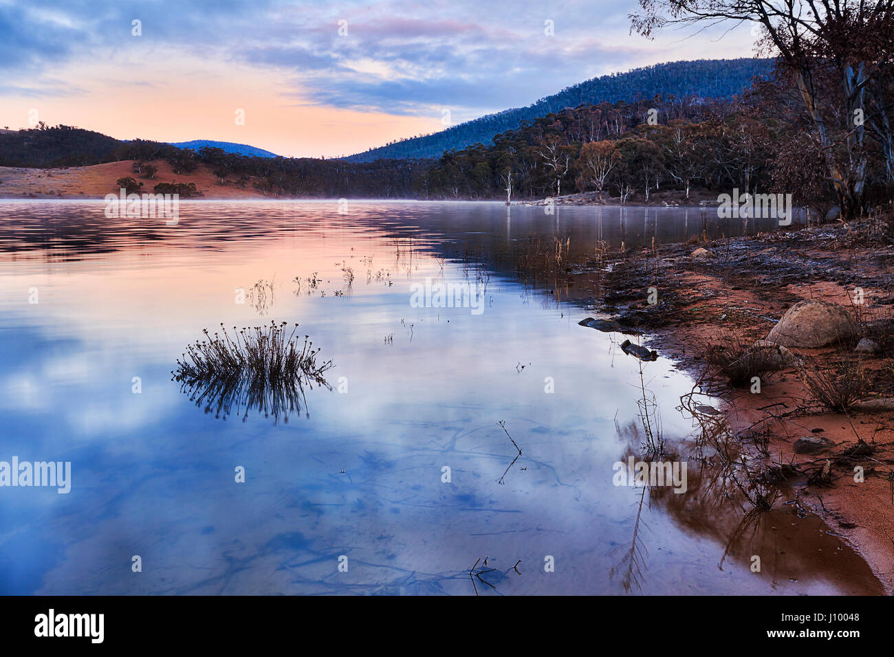 Pink sunrise over hills change around Jindabyne lake in Snowy mountains national park of Australia. Rising sun reflects - Stock Image