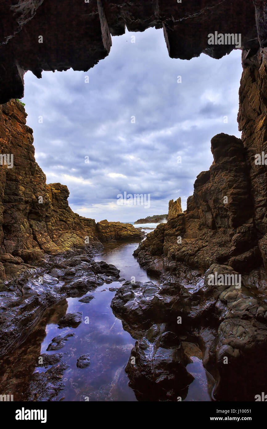 Rocky isolated grotto result of sea erosion at Cathedral rocks sandstone formation of Pacific coast in Australia - Stock Image