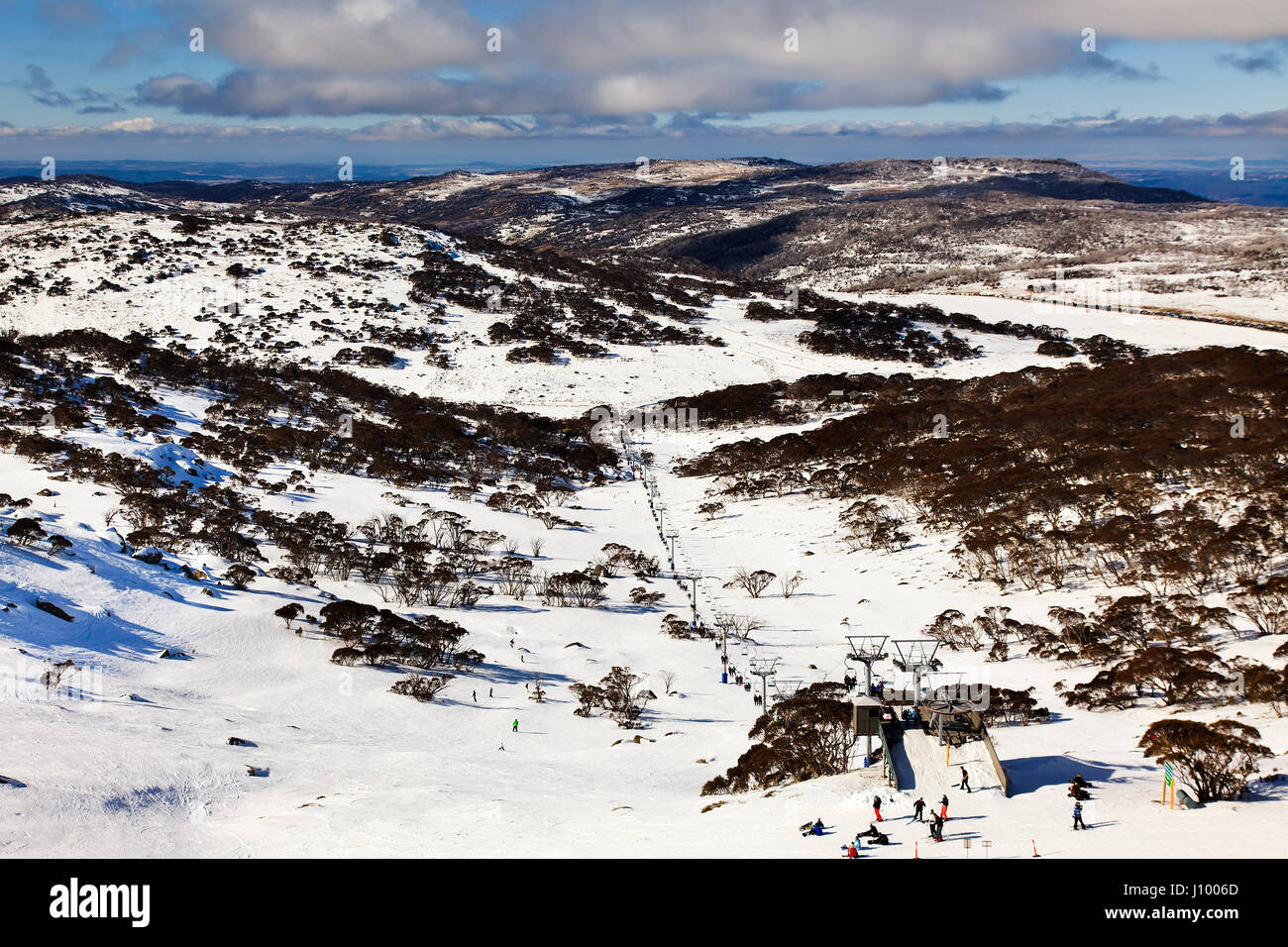 Elevated view on Perisher valley ski resort, cableway and relaxing skiers with snowboaders at high winter skiing - Stock Image