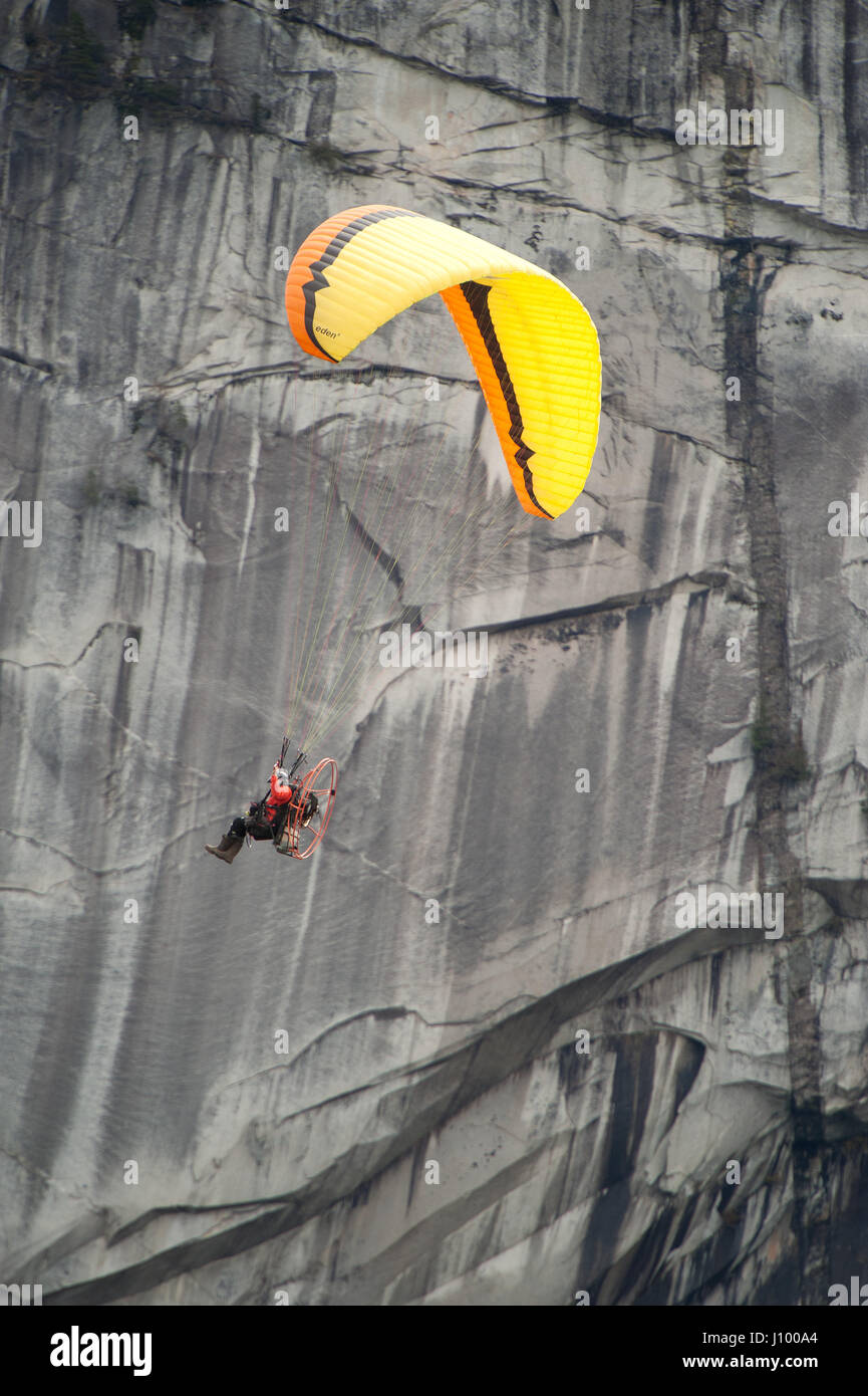 A man flies a motorized paraglider, or para motor past the Stawamus Chieftain and Shannon Falls.  Squamish BC, Canada. - Stock Image