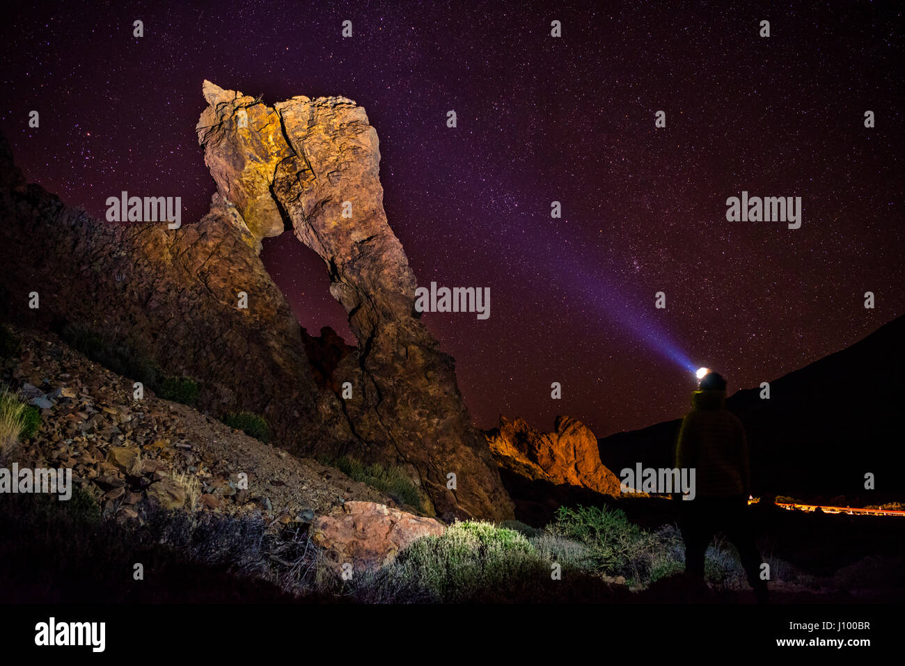 Man with headlamp, flashlight, standing in front of Zapato de la Reina, Queen's shoe, rock formation - Stock Image