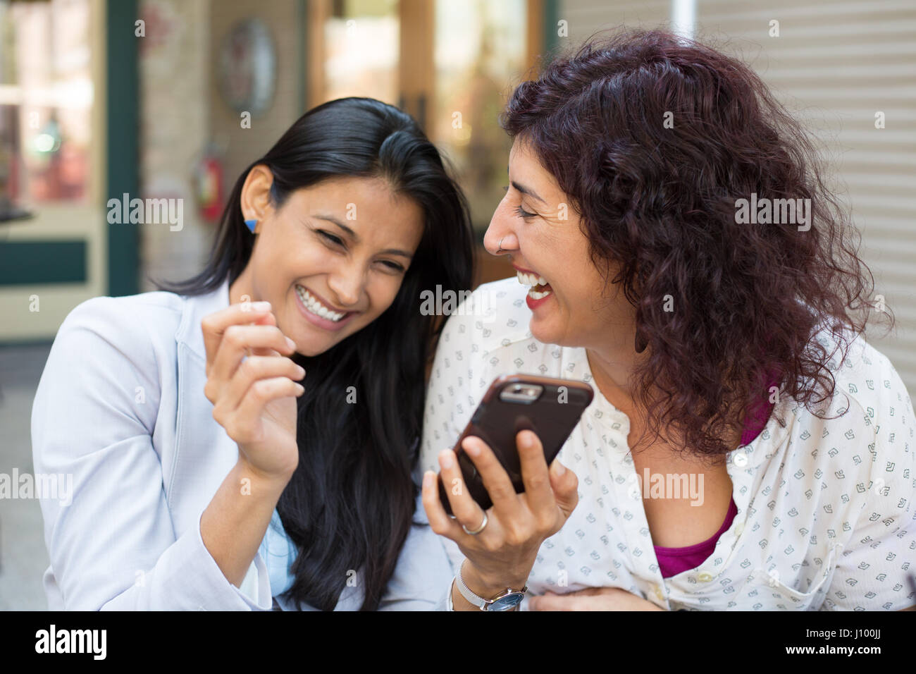 Closeup portrait two surprised girls looking at cell phone, discussing latest gossip news, sharing intimate moments, - Stock Image