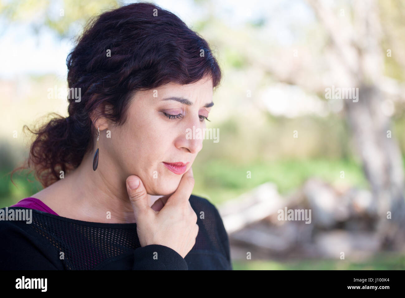 Closeup portrait of philosophical thinking dark hair woman hand on chin, deep in thought, isolated outside outdoors - Stock Image