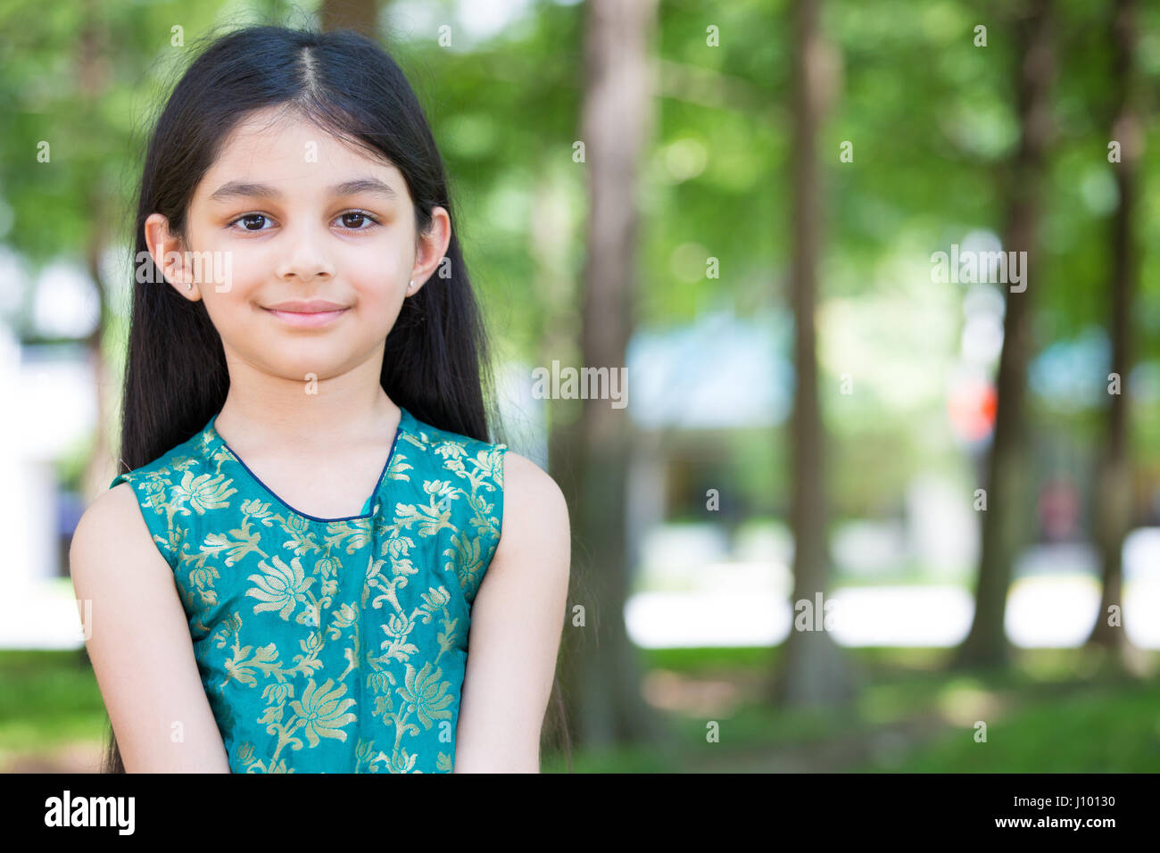 Closeup portrait, young girl standing in forest on sunny day, isolated outside outdoors background - Stock Image