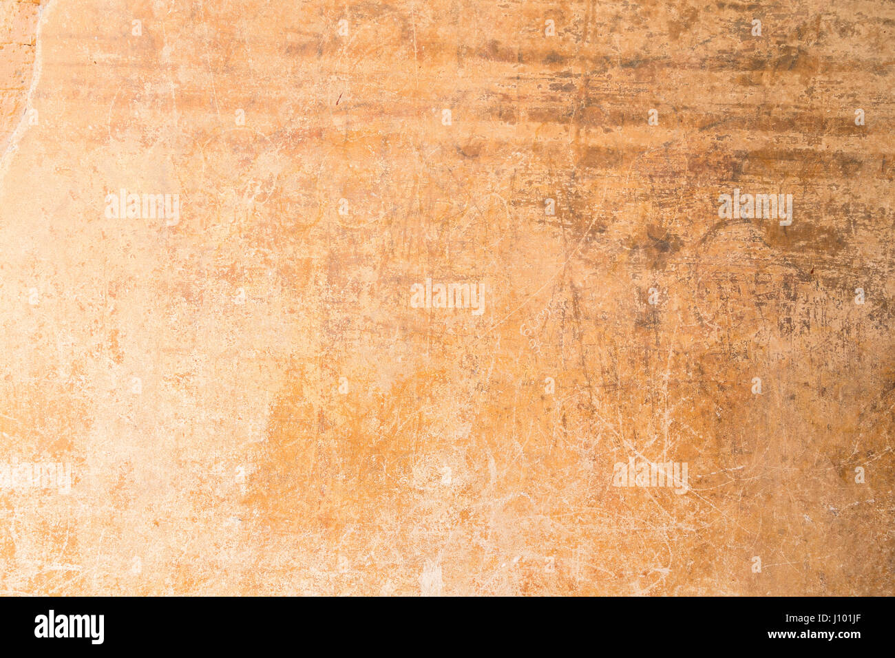 Weathered, aged and scratched orange concrete wall texture background. - Stock Image