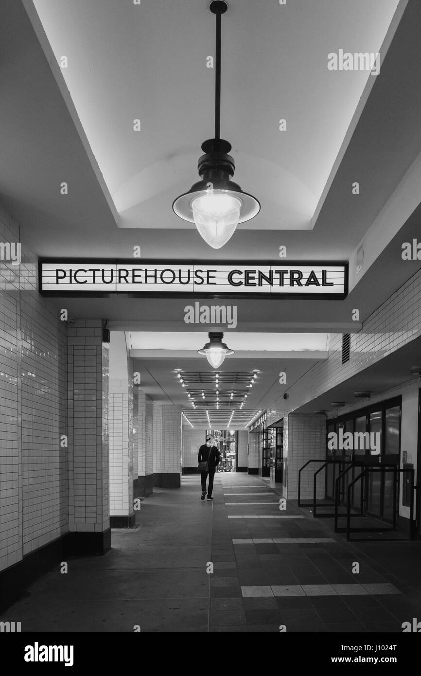 Black and white image of a man walking towards the Picturehouse Central Cinema and Cafe, London. - Stock Image