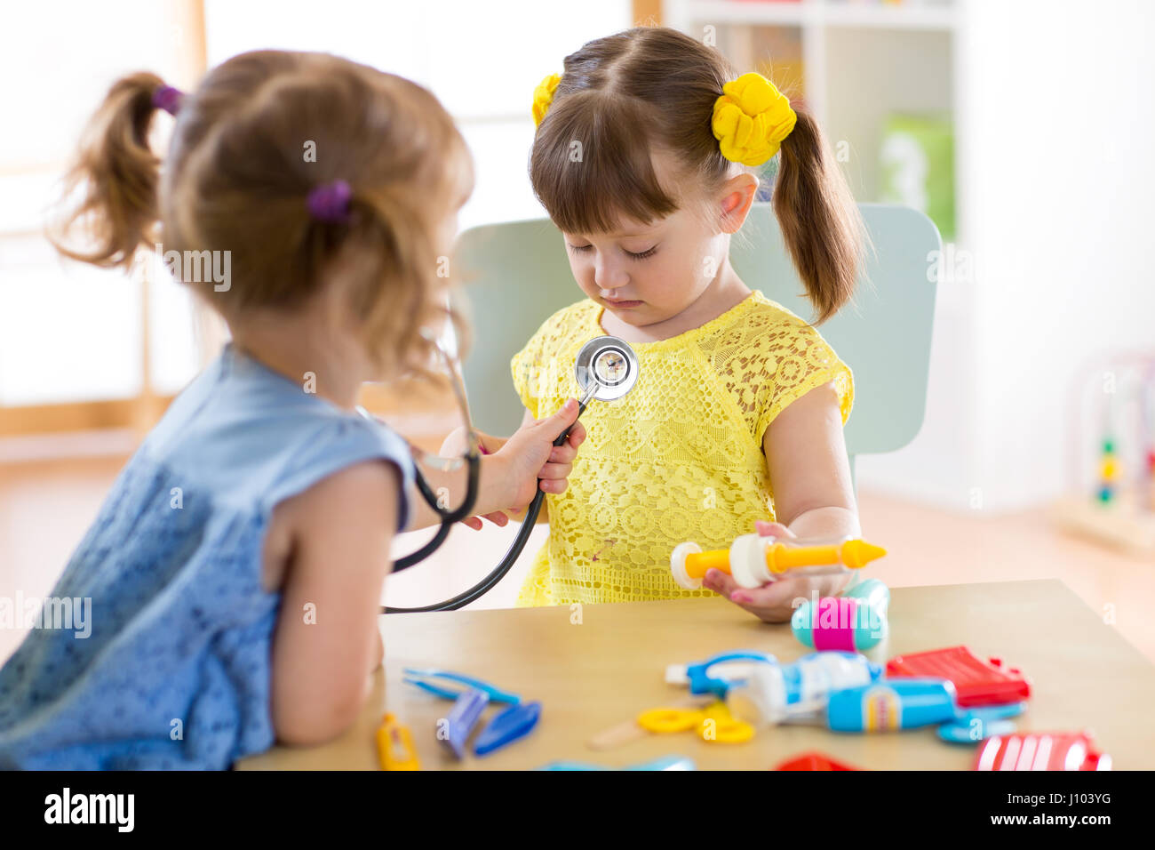 two cute children play doctor and hospital using stethoscope
