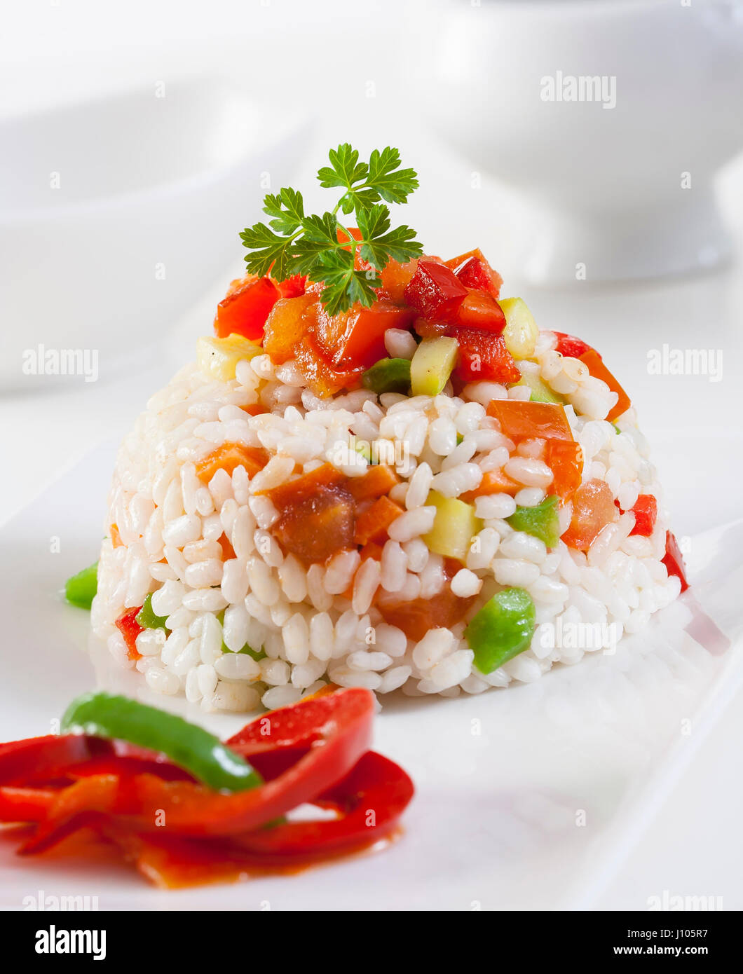 Rice with peas and red pepper. - Stock Image