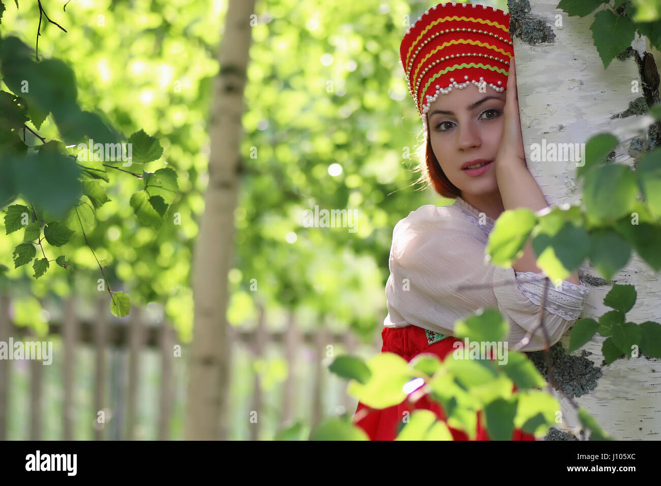 Slav in traditional dress hiding behind trees Stock Photo