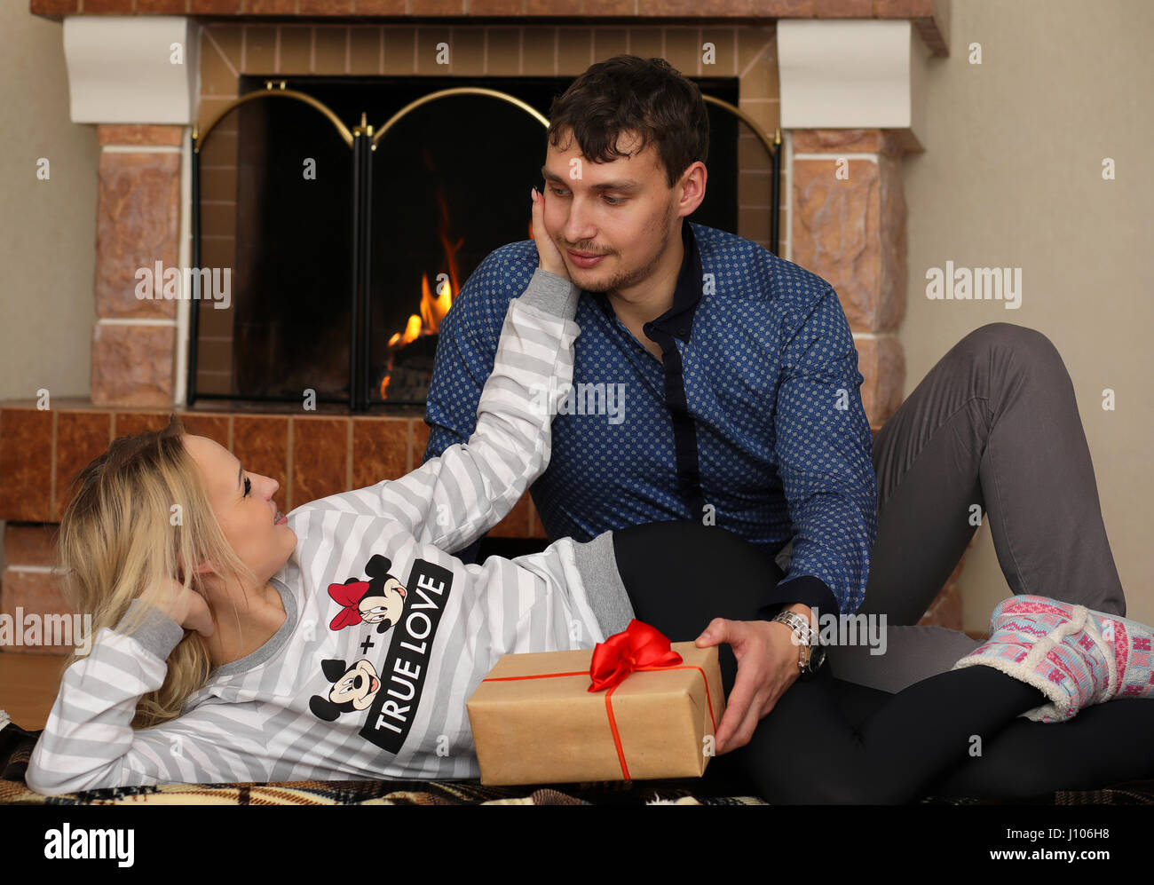 young couple relaxing near the burning fireplace - Stock Image