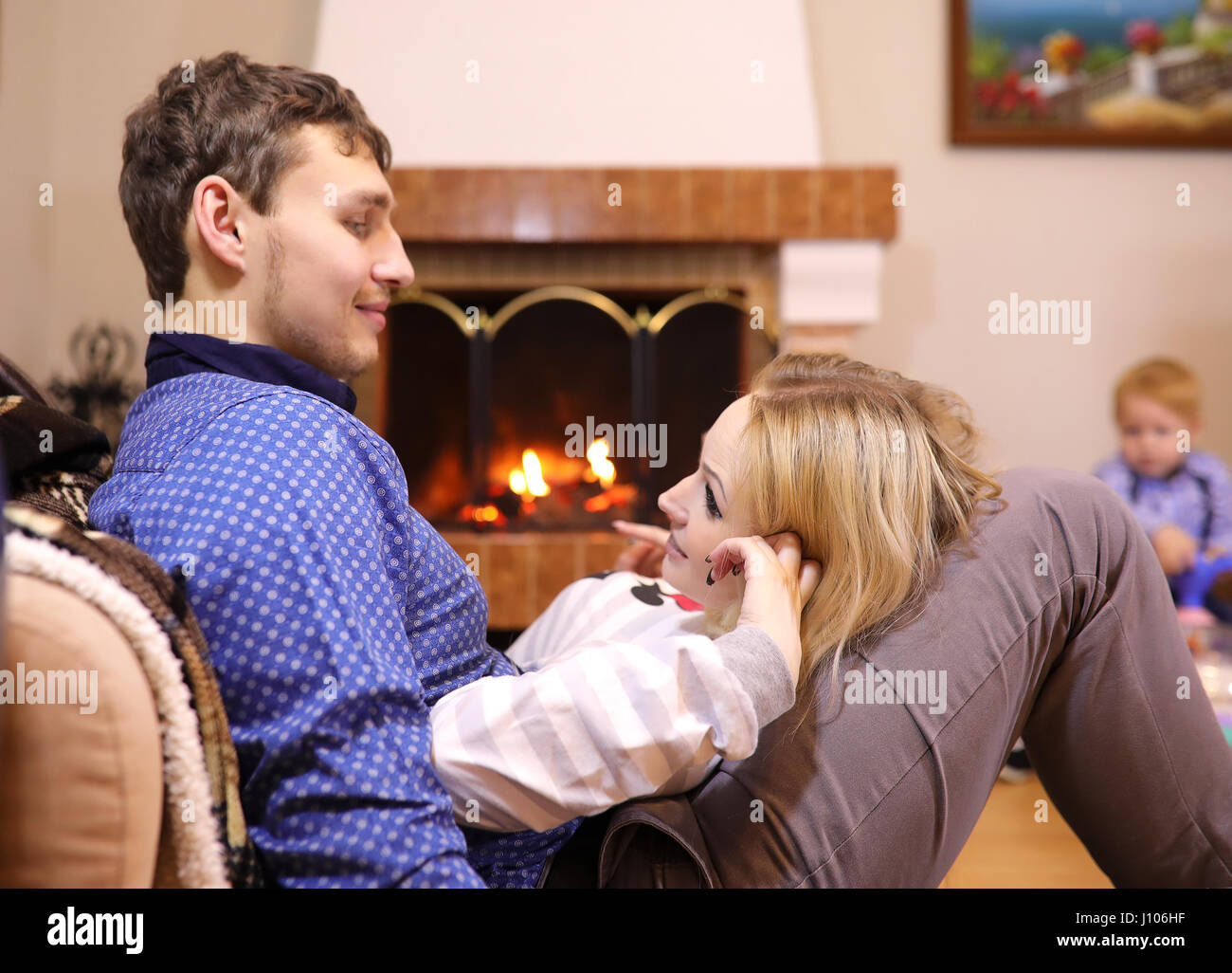 family warmed by the fireplace sitting on the couch - Stock Image