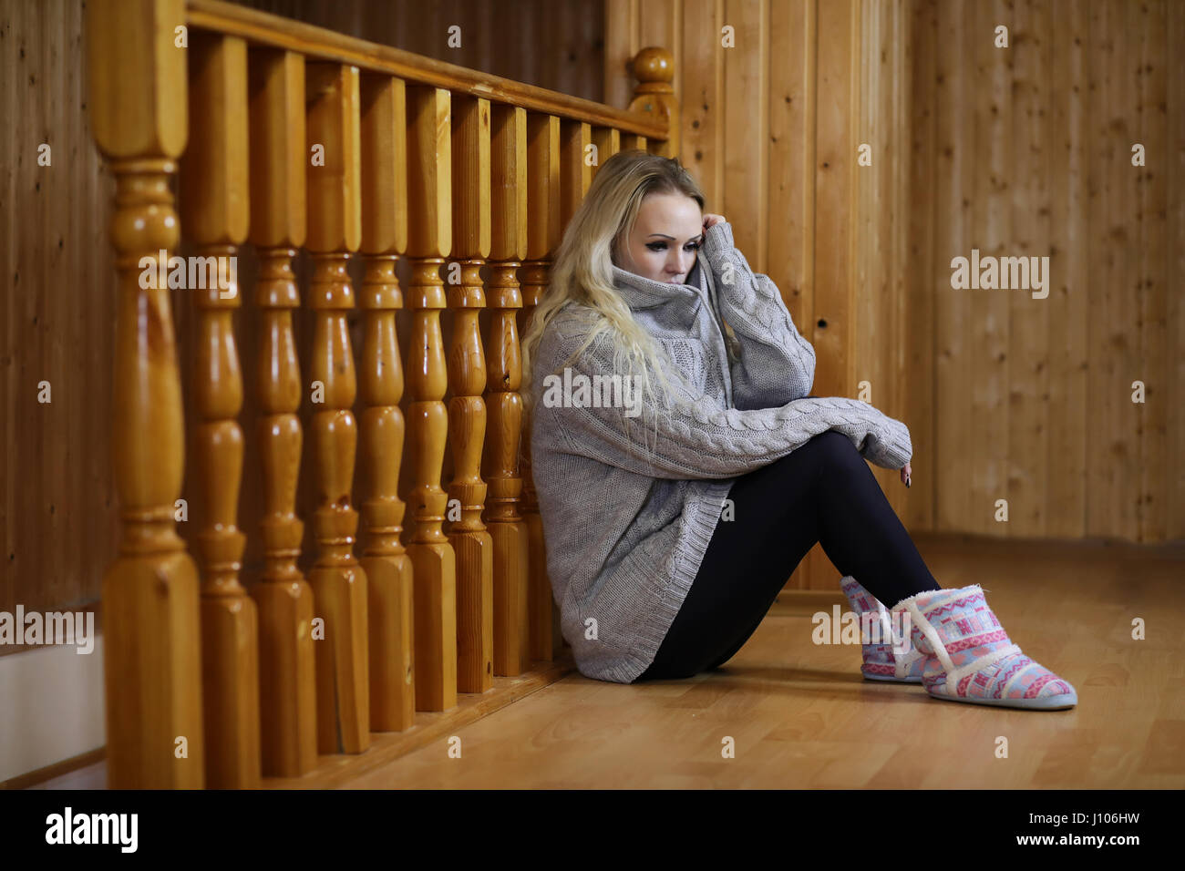 girl sitting on the floor near the wooden railing Stock Photo