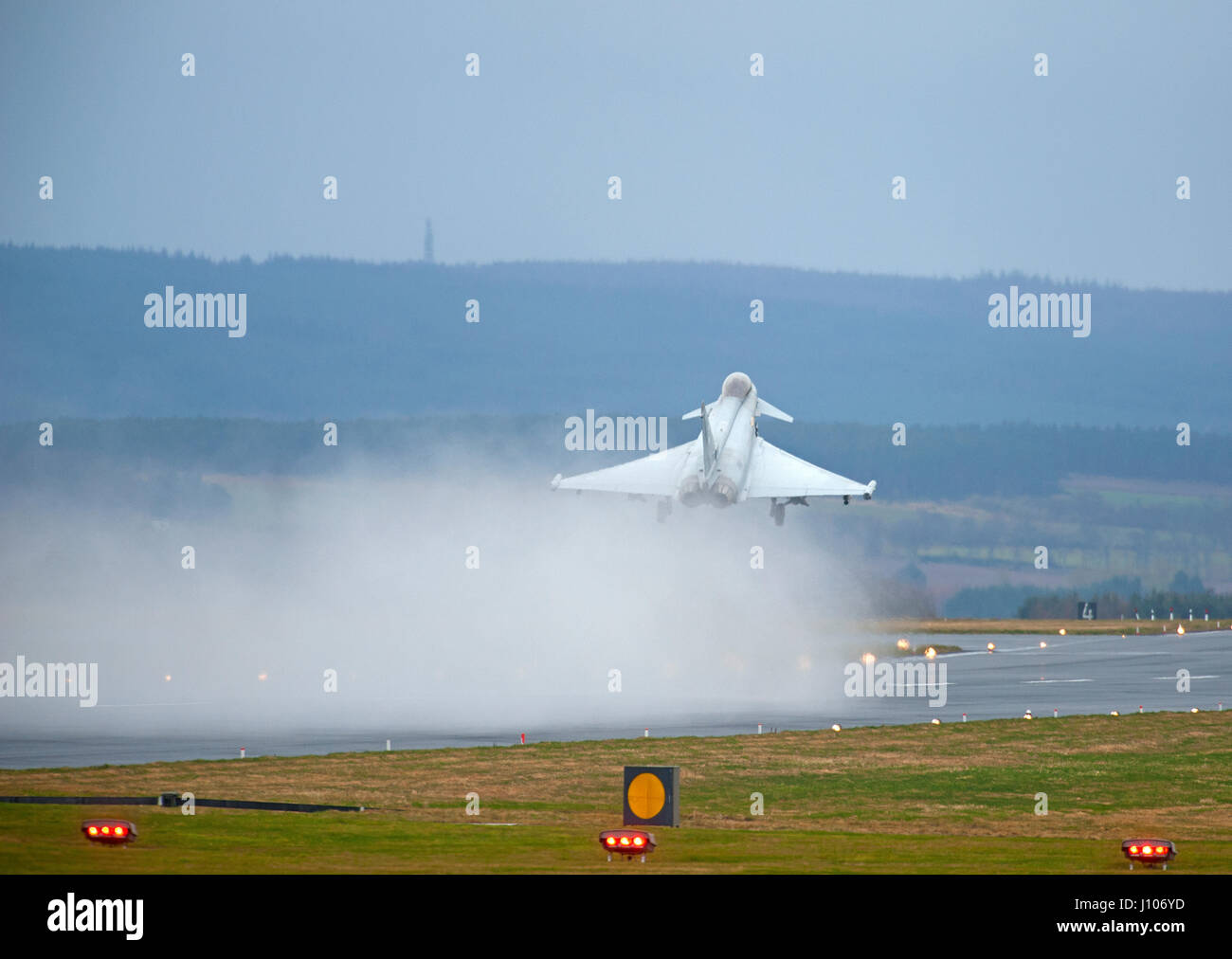 Eurofighter Typhoon taking off from a wet RAF Lossiemouth runway in Morayshire, Scotland. - Stock Image