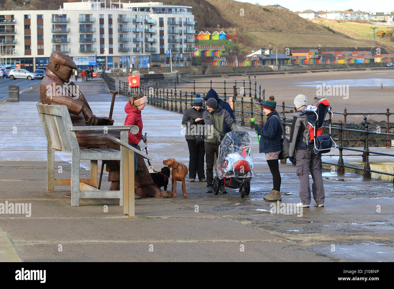 Tourists around the Freddie Gilroy sculpture on Scarborough's north bay - Stock Image