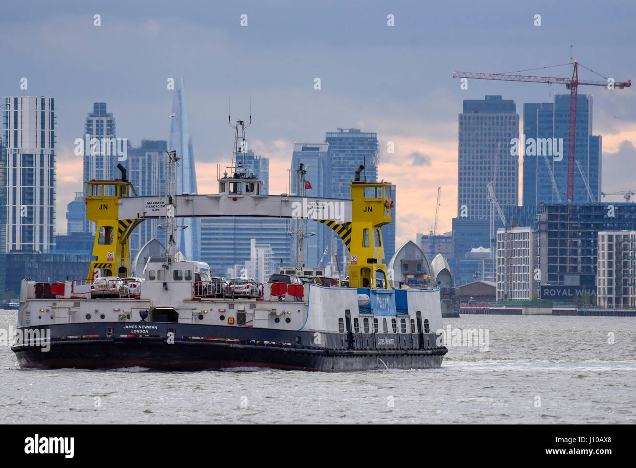 London, UK. 16th Apr, 2017. The Woolwich car ferry crosses the River Thames in front of the distant skyscrapers - Stock Image