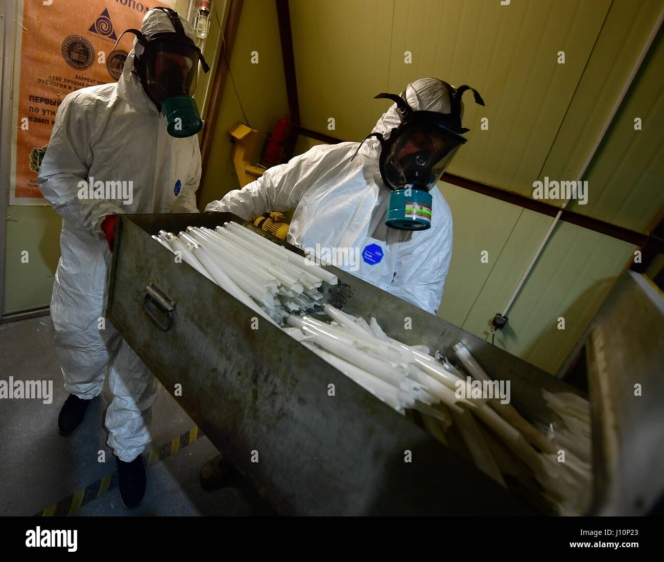VLADIVOSTOK, RUSSIA - APRIL 18, 2017: An employee wearing a gas mask recycles fluorescent lamps at the PrimTechnopolis - Stock Image