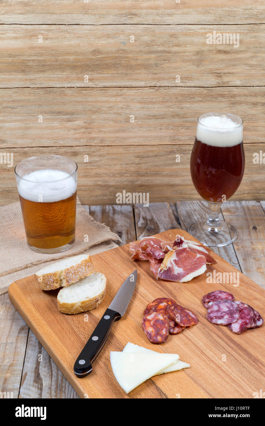 wooden board with sausage, cheese and beer glasses on an old wooden table Stock Photo