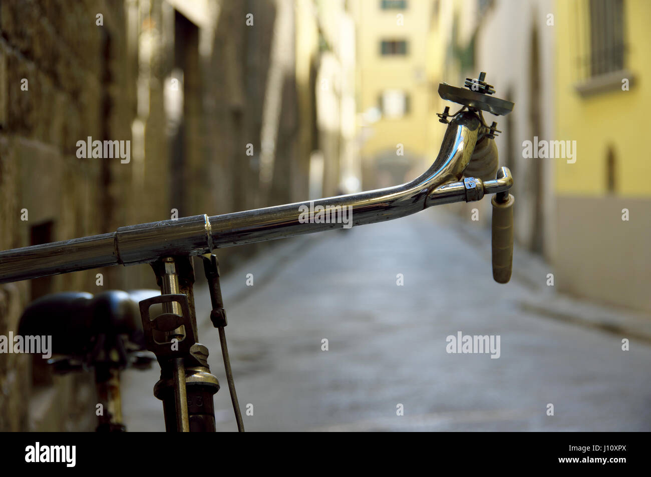Bicycle handlebar detail against a bokeh alley in central Florence (Firenze), Tuscany, Italy, Europe - Selective - Stock Image