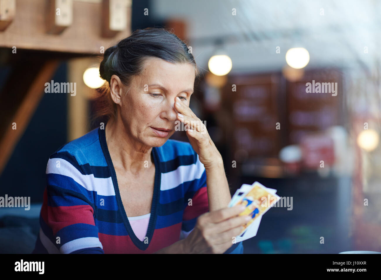 Mature female reminiscing her relatives and crying - Stock Image