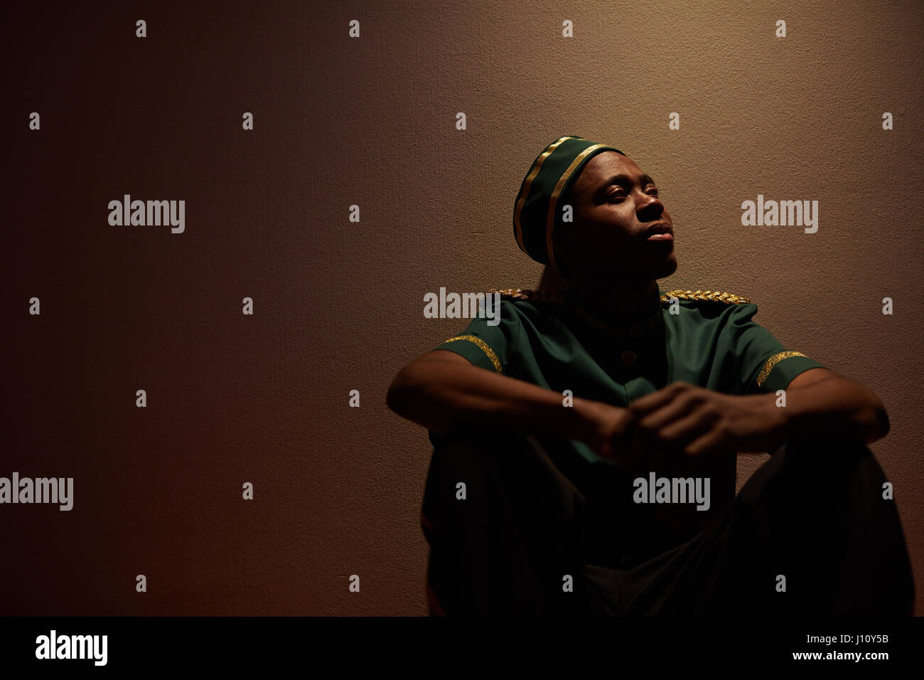 Young African-american bellboy sitting by wall of hotel - Stock Image